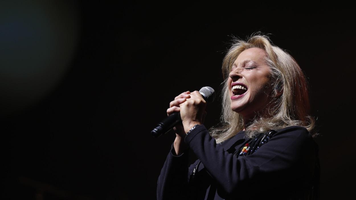 La chanteuse française Véronique Sanson tient son micro à deux mains et chante en fermant les yeux.