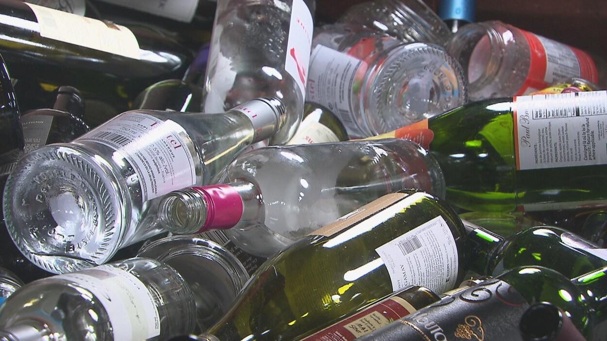 Des bouteilles de vin et autres contenants en verre empilés les uns par dessus les autres.