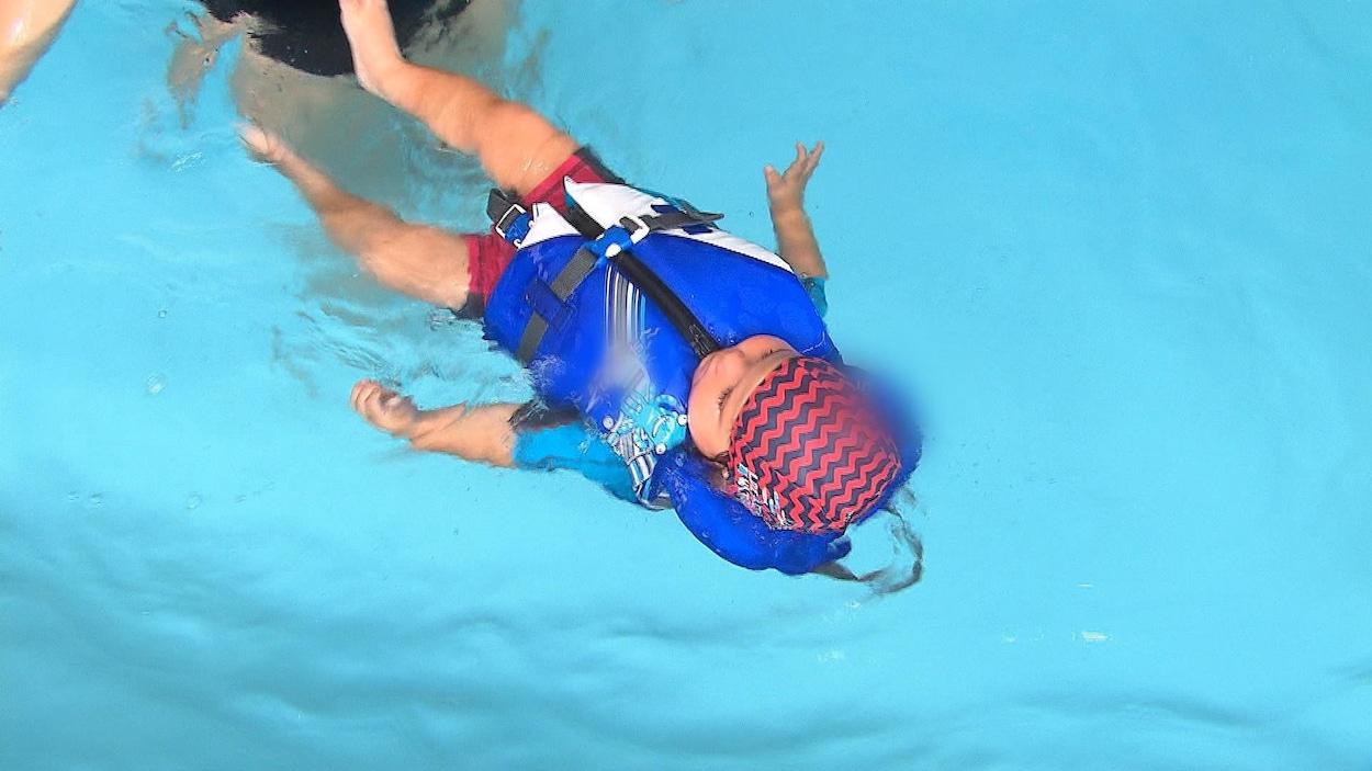 Un bébé flottant dans une piscine à l'aide d'une veste de flottaison.
