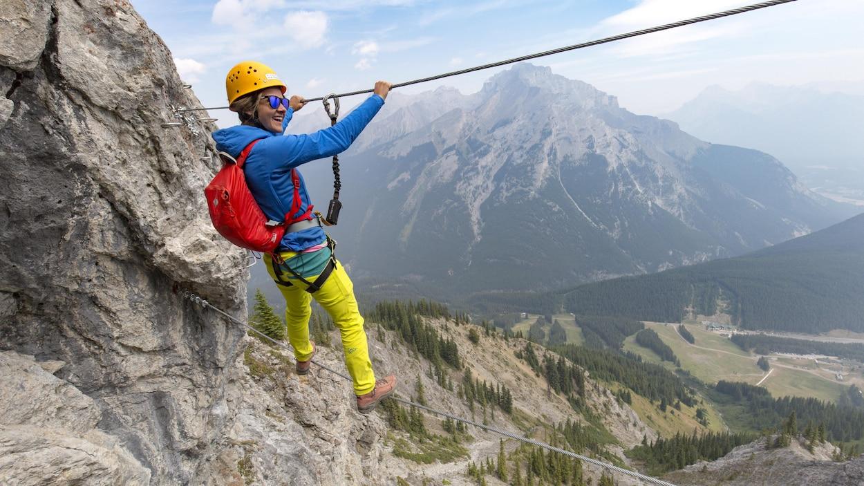 Une femme emprunte une passerelle en haute altitude. En arrière-plan, des montagnes rocheuses.