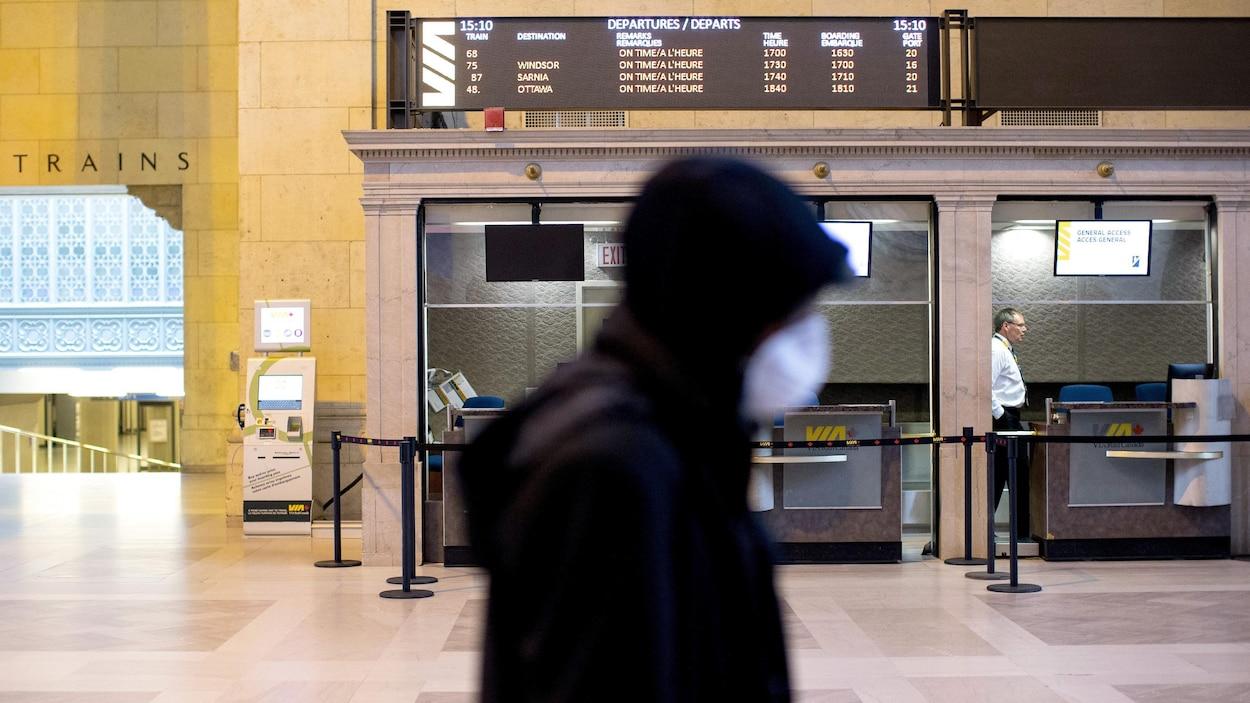 Un homme masqué passe devant un comptoir de VIA Rail à la gare Union de Toronto.