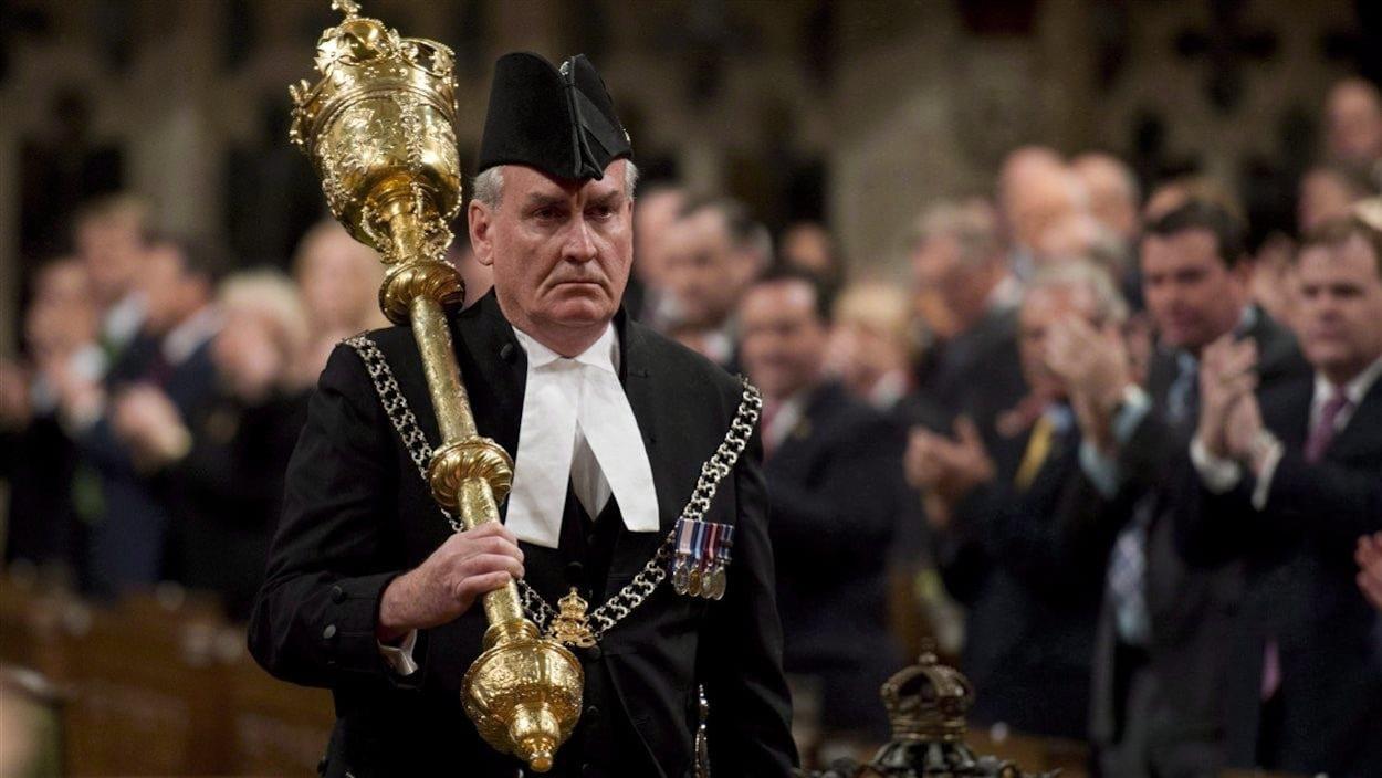 Kevin Vickers marche dans la Chambre des communes en portant sur son épaule la massue traditionnelle du sergent d'armes, tandis que les députés sont debout pour l'applaudir.