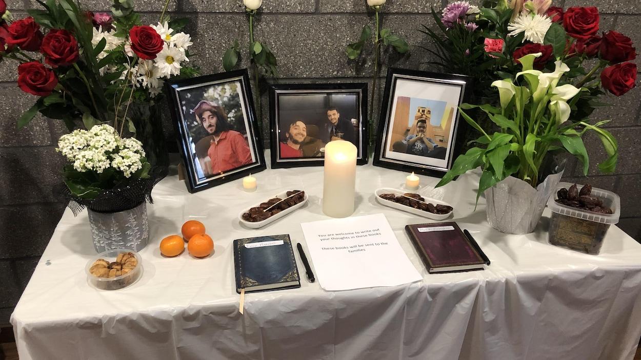 Des portrait des hommes avec des chandelles, des fleurs et des denrées sont installés sur une table avec une nappe blanche.