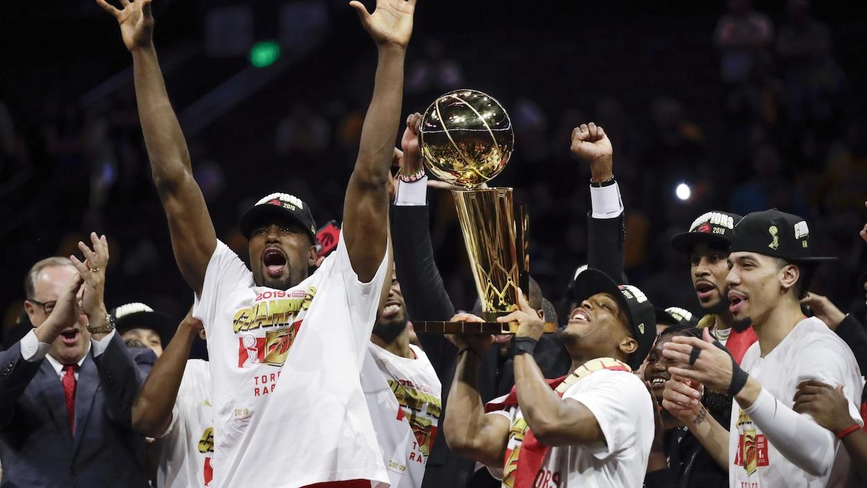 Des joueurs des Raptors de Toronto célèbrent en soulevant un trophée.