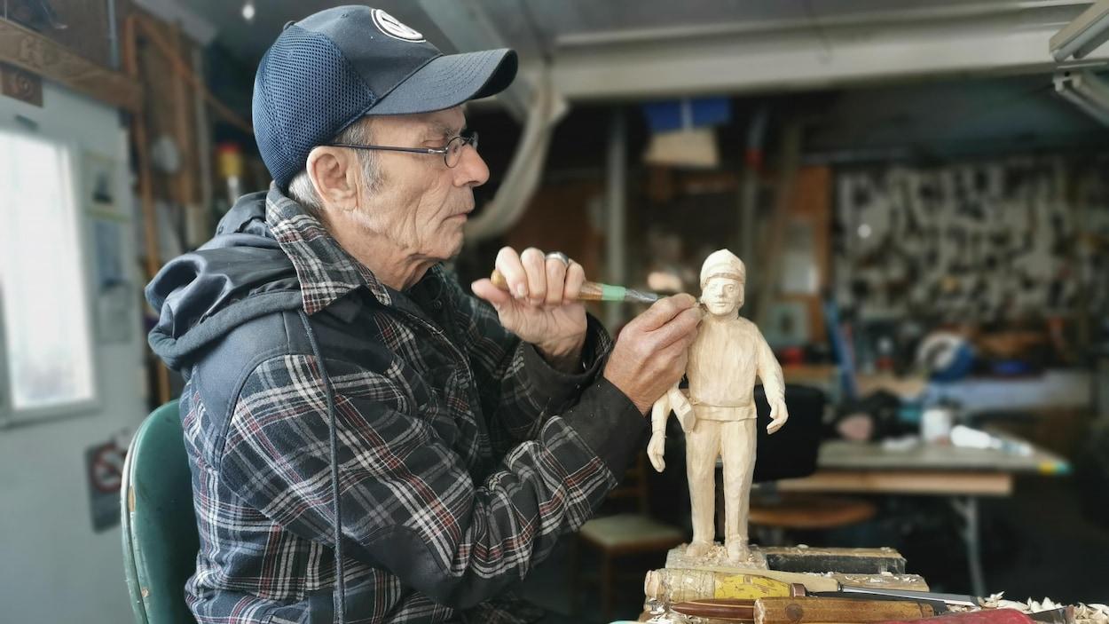 Victor Dallaire taille le corps d'un homme dans une pièce de bois.