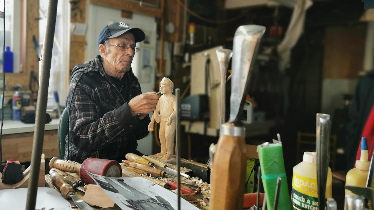 L'artiste Victor Dallaire sculpte un personnage en bois dans son atelier.