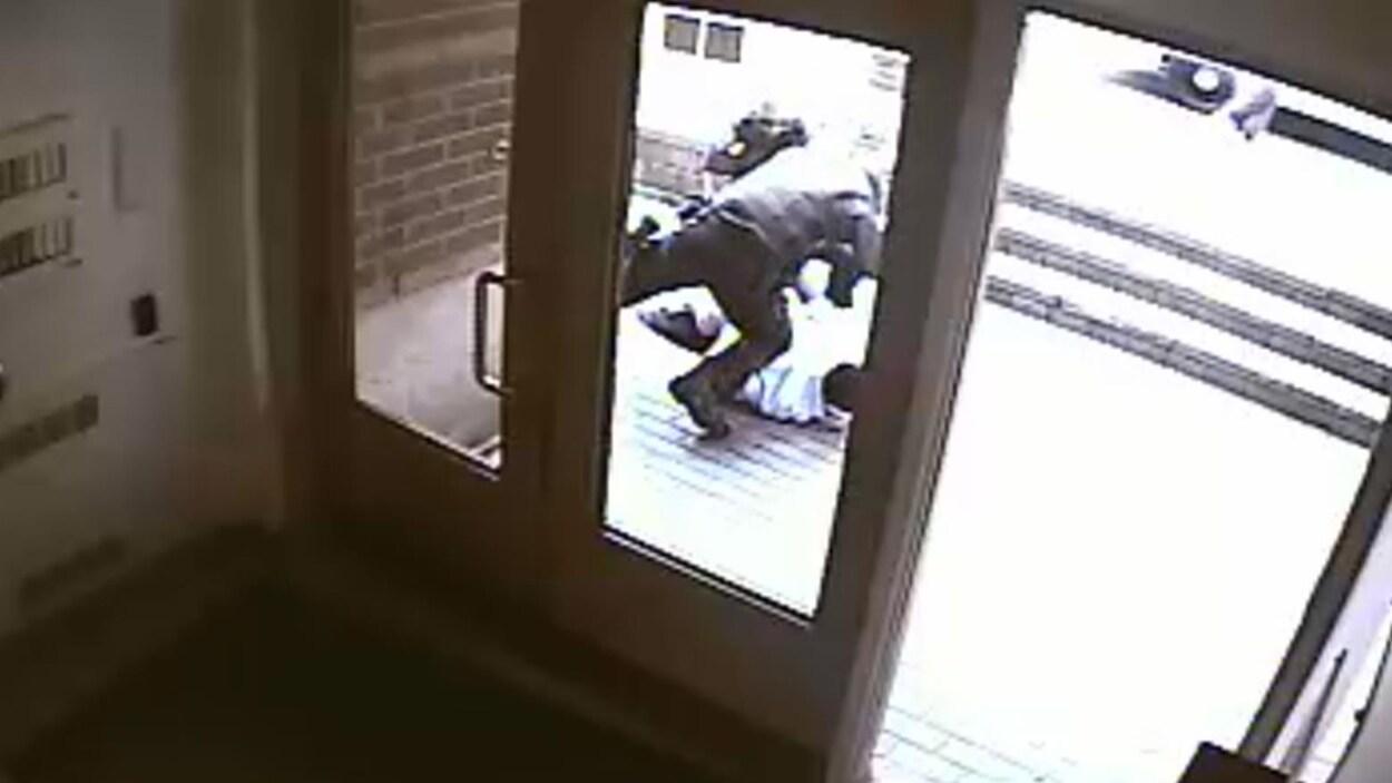 Sur l'image, on peut voir un policier frapper un homme debout.