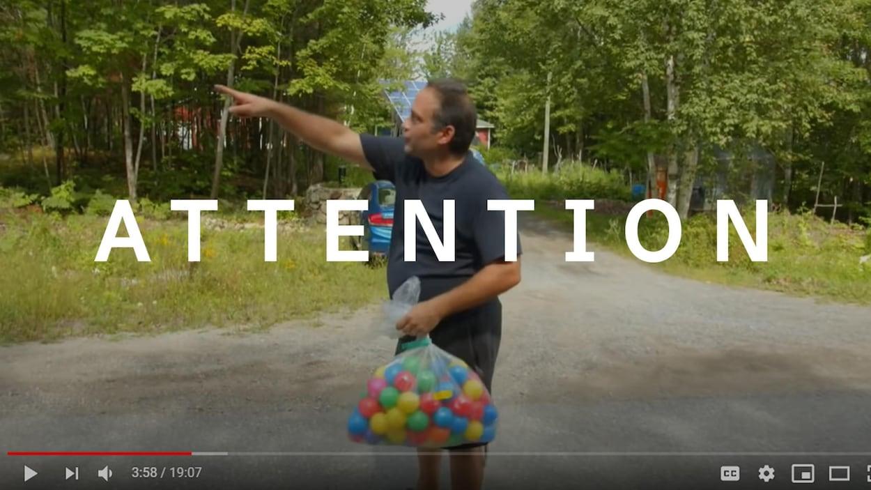 Un homme tient un sac rempli de balles de plastique.