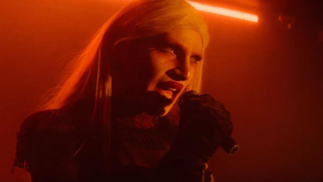 La drag queen porte une perruque blonde et fait semblant de chanter au micro.