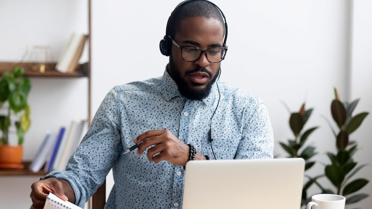 Un homme en parle en regardant son ordinateur portable. Il porte des écouteurs