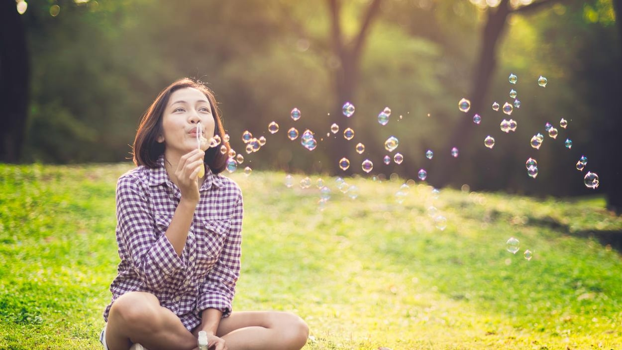 Une jeune femme fait des bulles.