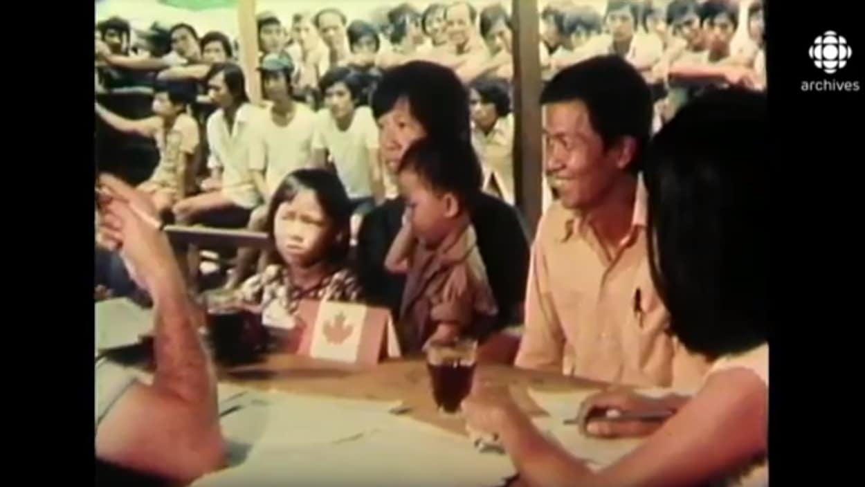 Une famille vietnamienne, assise à une table, rencontre des agents de l'immigration canadienne.