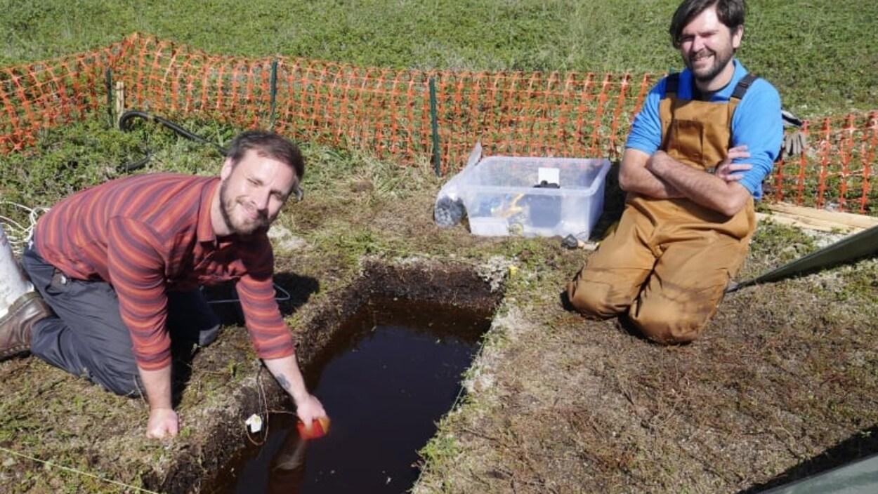 Deux hommes et un trou qu'ils ont creusé dans la terre.