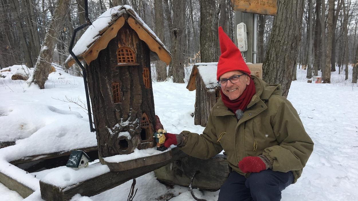 Un homme souriant s'agenouille pour poser avec un petit gnome et une bûche modifiée en petite maison.