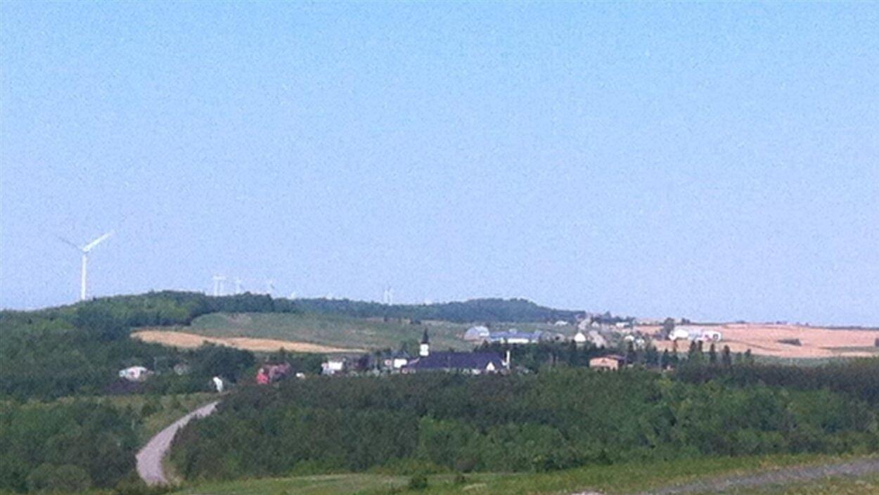 Le village de Saint-Léandre est bordé, d'un côté, d'une série de tours d'éoliennes, et de champs, de l'autre.