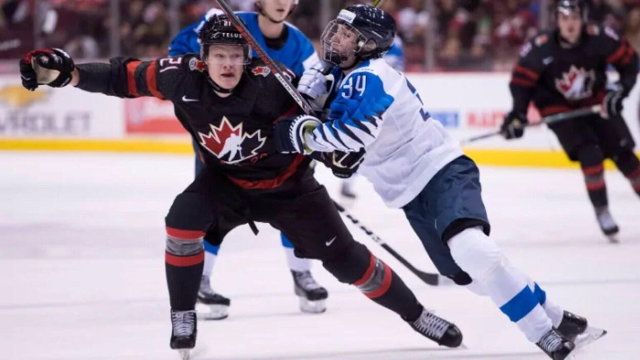 À gauche, un joueur de hockey avec l'habit du Canada. À droite, un joueur de hockey habillé aux couleurs de la Finlande.