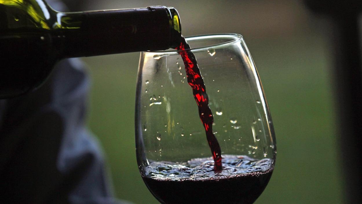 Du vin est versé d'une bouteille à un verre.