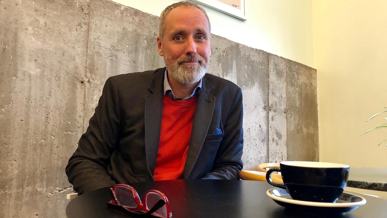 Vincent Marissal assis à une table, où sont déposées des lunettes et un bol de café.