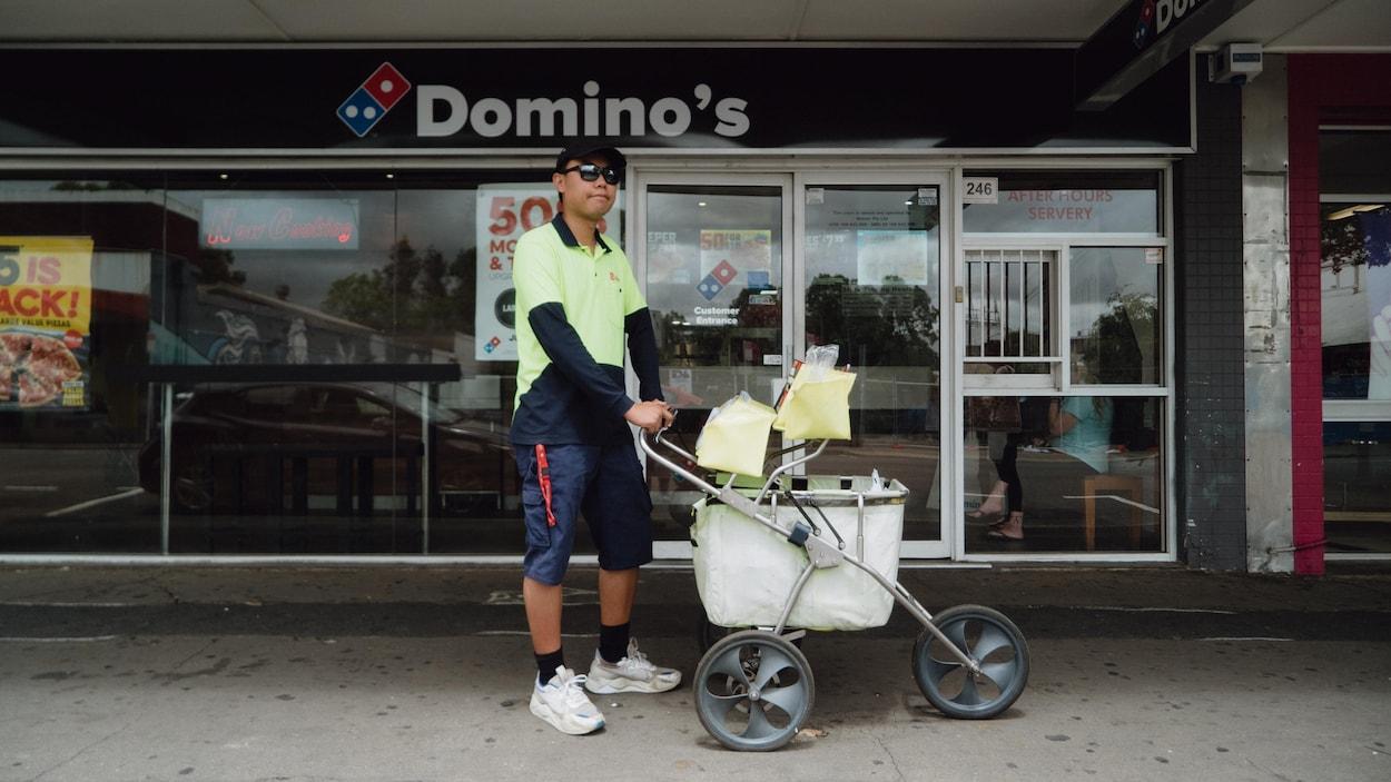 Un postier pousse son charriot de courrier sur un trottoir en banlieue de Sydney.