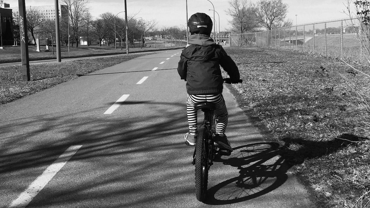 Le petit garçon vu de dos sur son vélo.