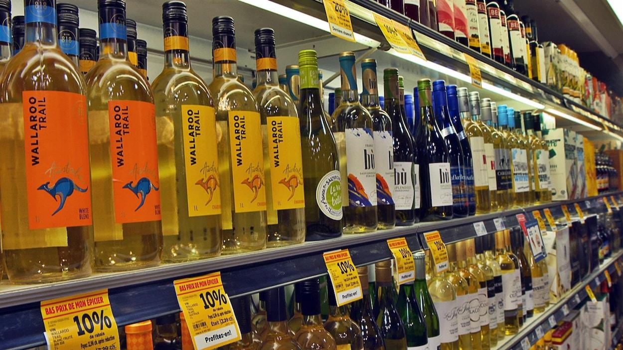 Des rangées de bouteilles de vin dans une épicerie.