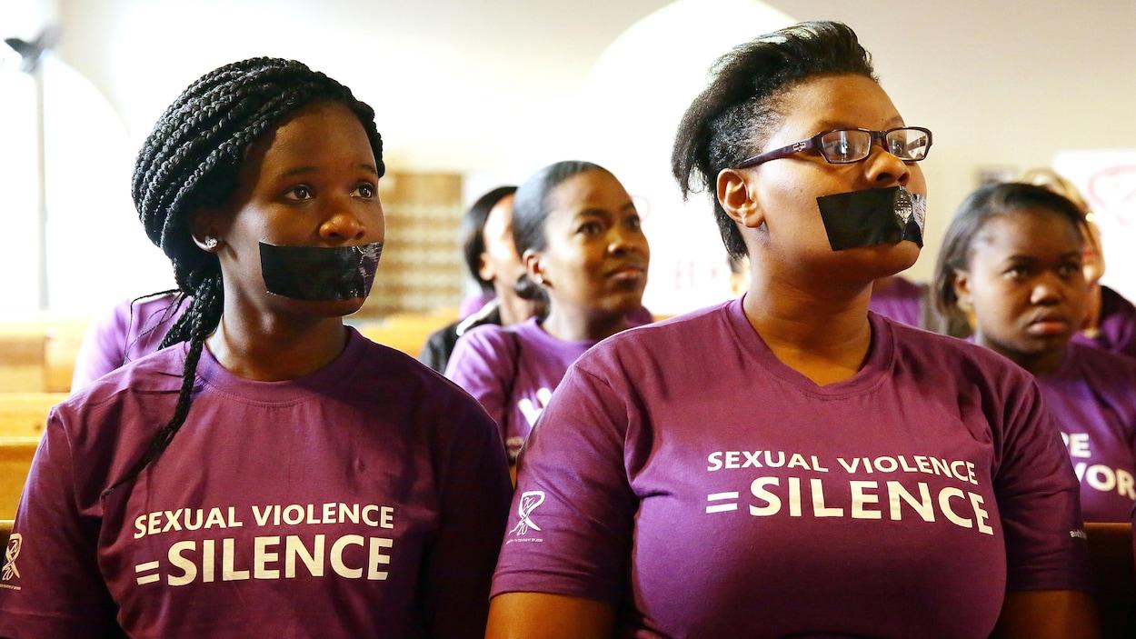 Elles ont la bouche couverte de ruban adhésif noir et portent un chandail sur lequel est écrit « Violence sexuelle = silence ».