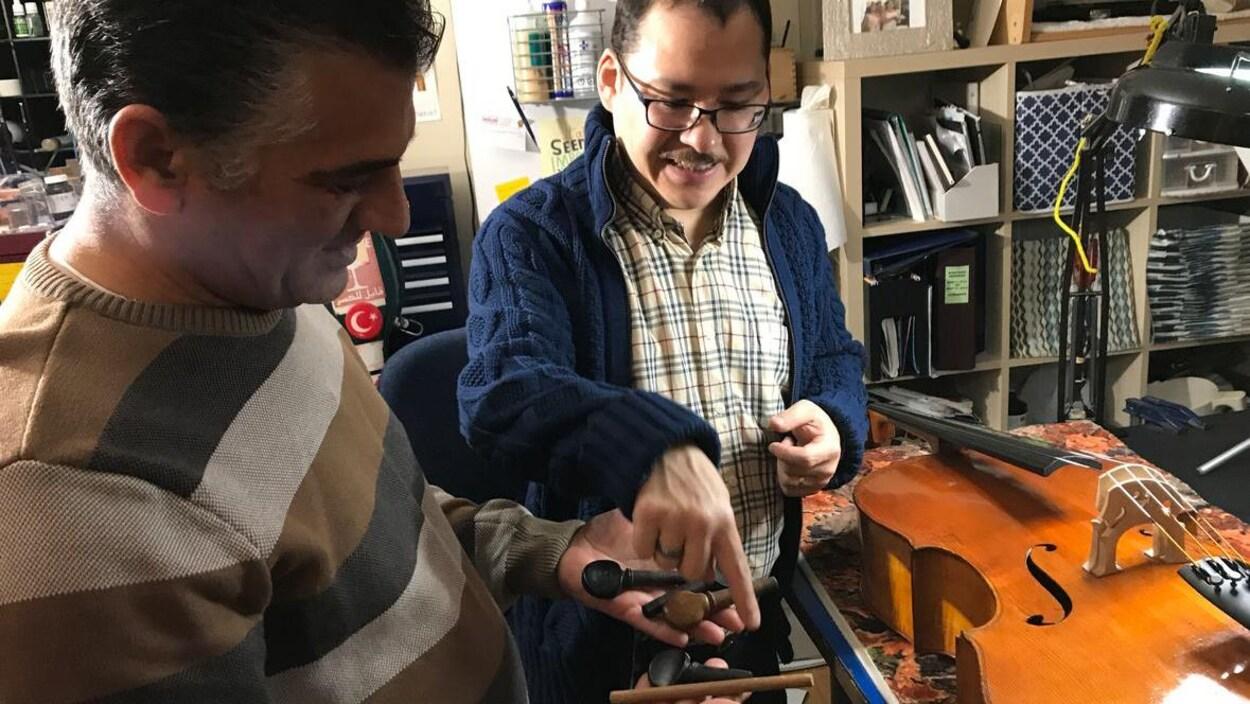Deux hommes regardent et choisissent des chevilles de bois pour tenir les cordes d'un violoncelle posé sur une table, dans l'atelier d'un luthier.