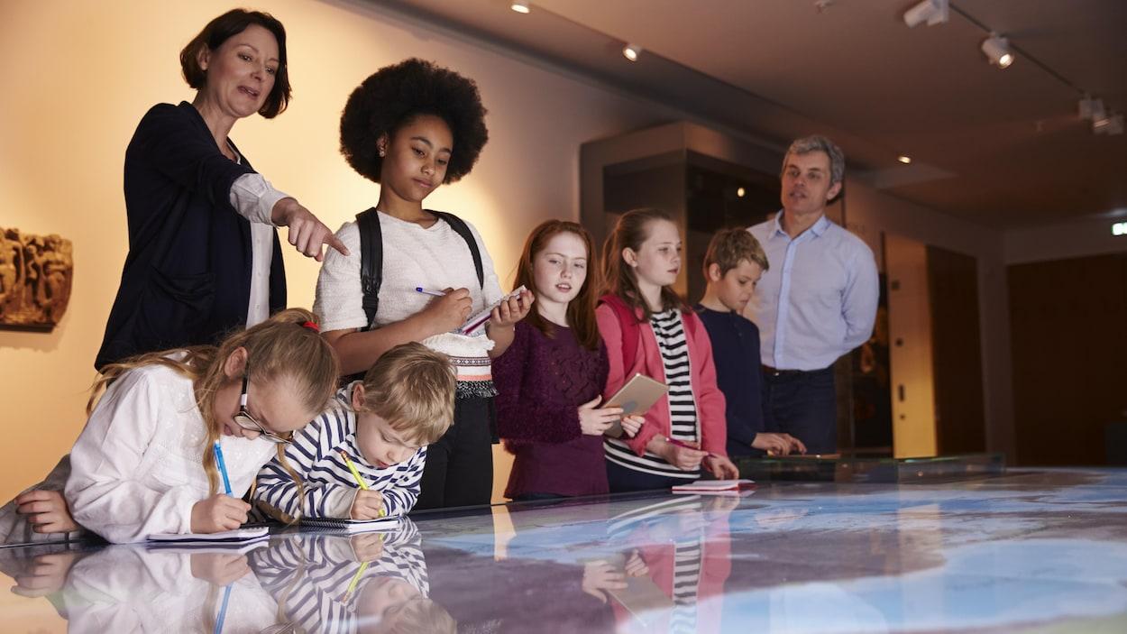 Des enfants en visite au musée regardent une carte.