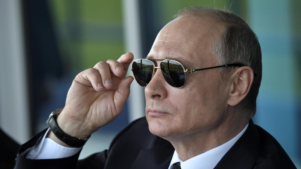 Le président russe Vladimir Poutine affiche une mine sévère derrière ses lunettes fumées.