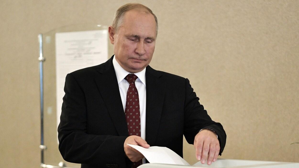 Vladimir Poutine place un bulletin dans une urne.