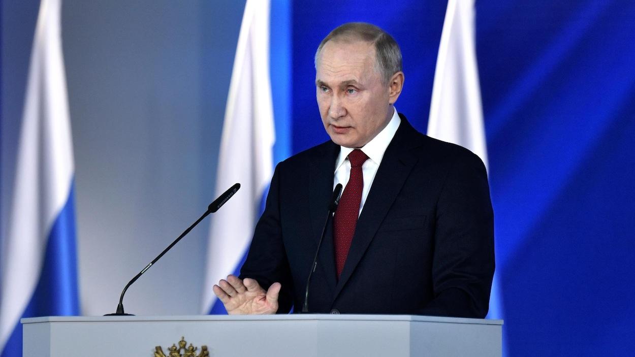 Vladimir Poutine parle derrière un lutrin, plusieurs drapeaux russes se trouvent derrière lui.