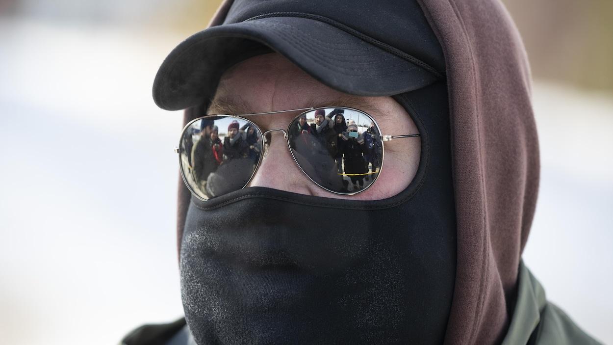 Plan rapproché d'un homme cagoulé dont les lunettes reflètent les journalistes devant lui.