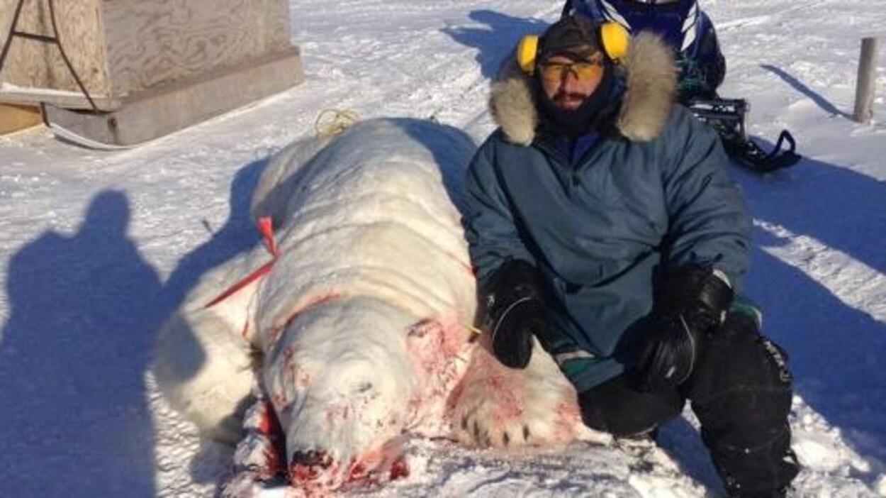 Darrell Voisey assis à côté de la carcasse d'un ours blanc.