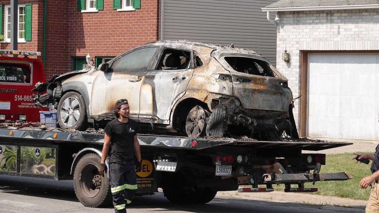 Un employé d'une entreprise de remorquage marche devant la carcasse calcinée d'une voiture.