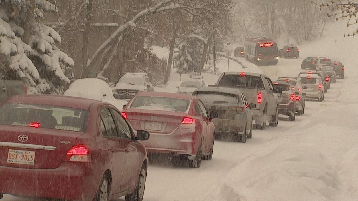 Une file de voitures sous la neige