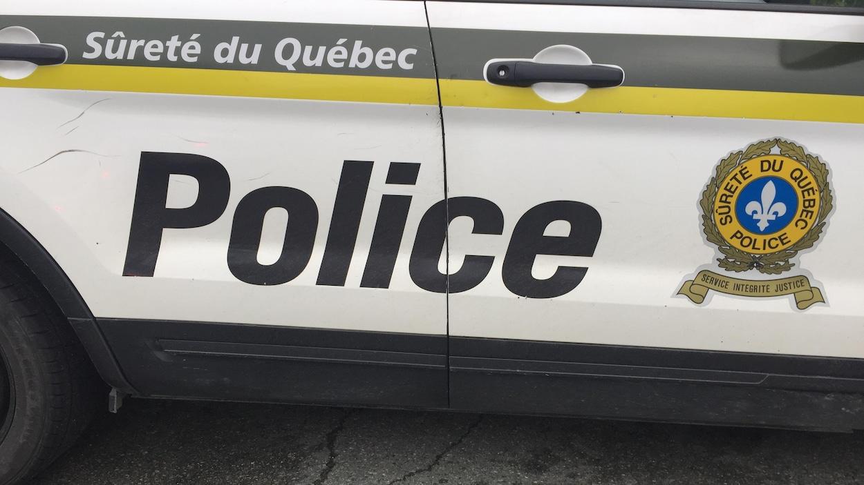Porte d'une voiture de police de la Sûreté du Québec avec le logo.