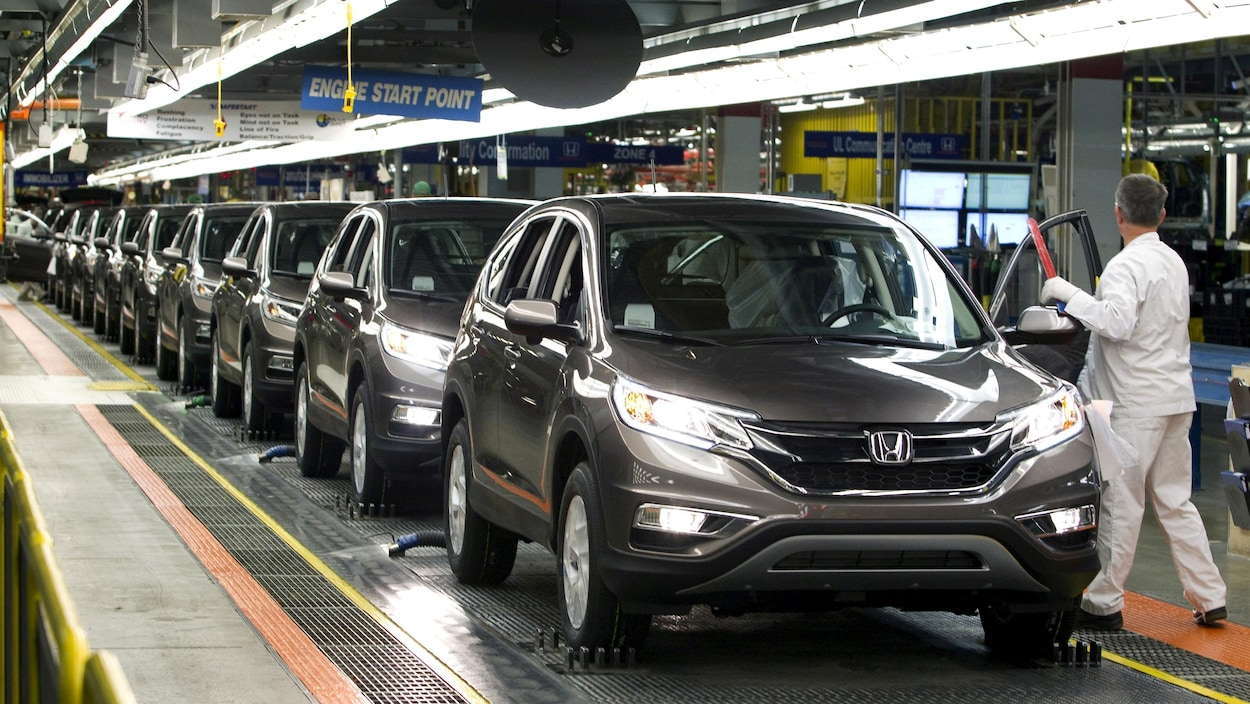 Un employé d'un fabricant automobile inspecte une chaîne de montage.
