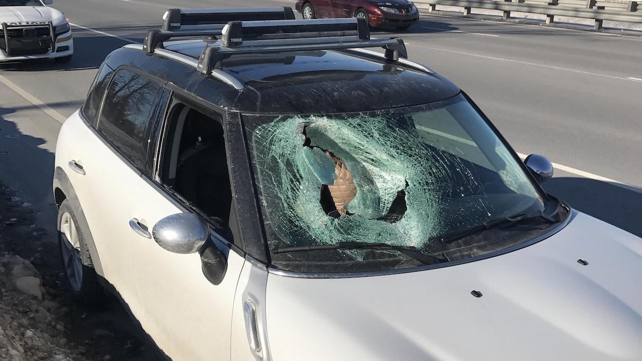 Le pare-brise de cette voiture a été lourdement endommagé par un morceau de glace en provenance d'un autre véhicule.