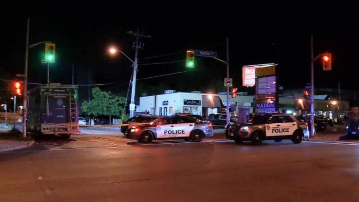 Des voitures de patrouille de police bloquent l'accès à une rue en plein milieu de la nuit dans le quartier nord-est de Toronto, North York. Les feux de circulation sont verts. Il y a aussi une banderole de sécurité jaune pour bloquer l'accès à  cette intersection de rues.