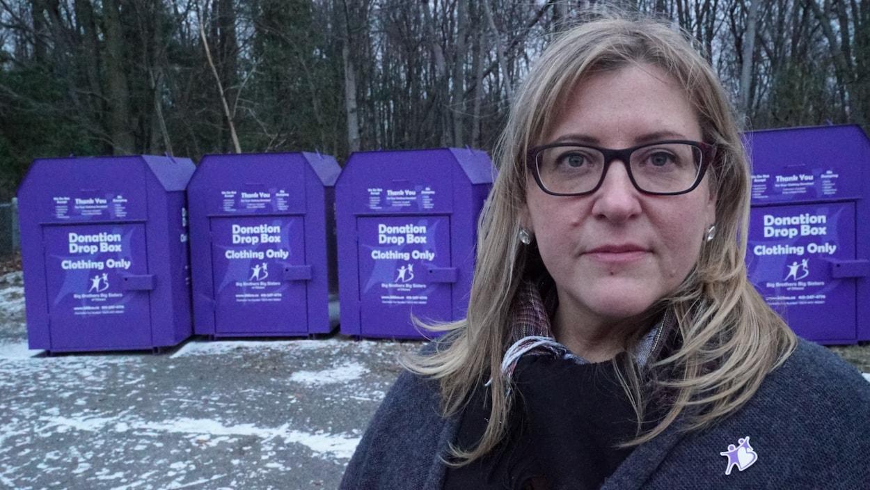 Une femme blonde devant des boîtes de dons mauves.