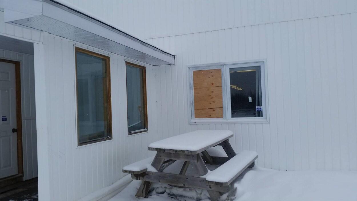 De l'extérieur, une fenêtre est placardée par une planche de bois.