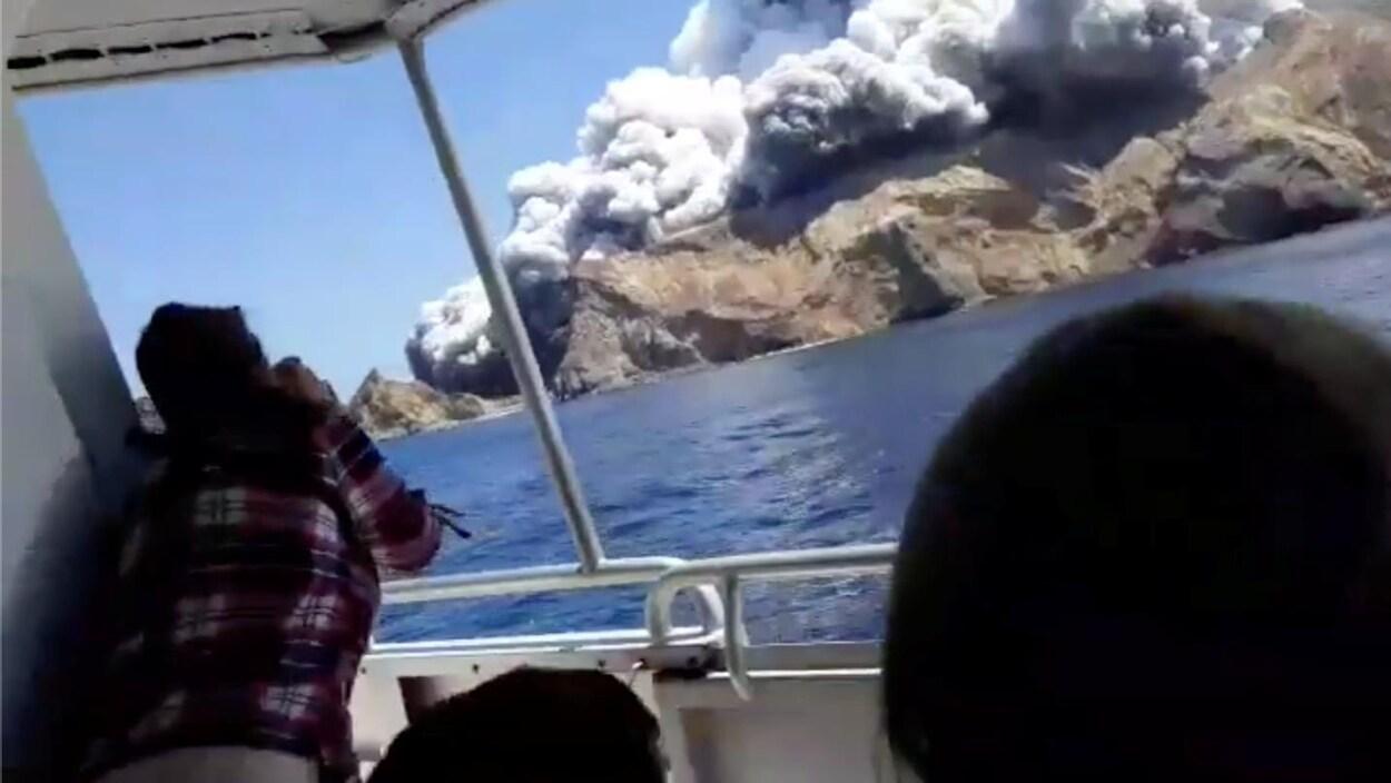 Un nuage de fumée sort d'un volcan en éruption, qu'une personne est en train de photographier depuis un bateau.
