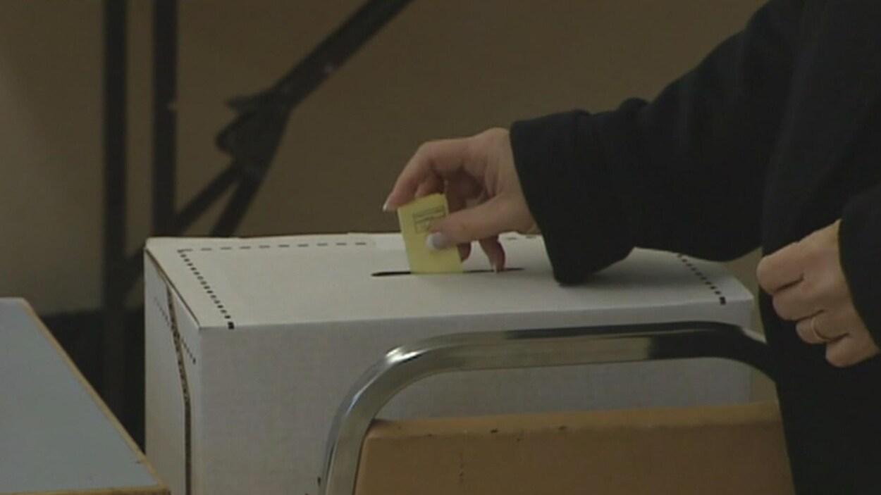 Une main de femme dépose un bulletin de vote dans une boîte de scrutin.