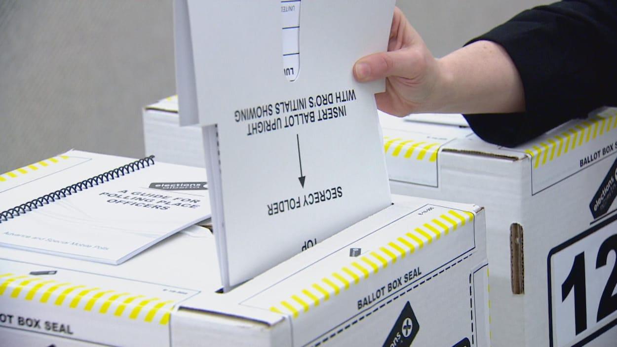 Un bulletin de vote rentre dans une boîte de crutin.