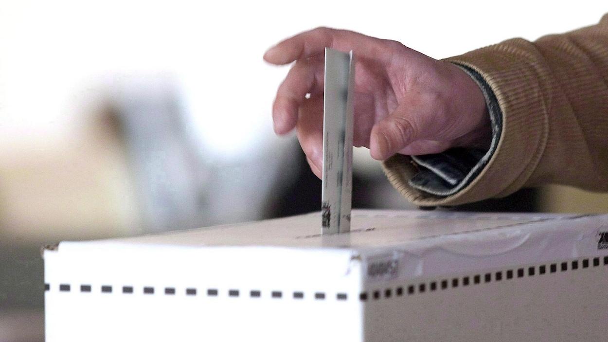 Un homme dépose son bulletin dans une boîte de scrutin.