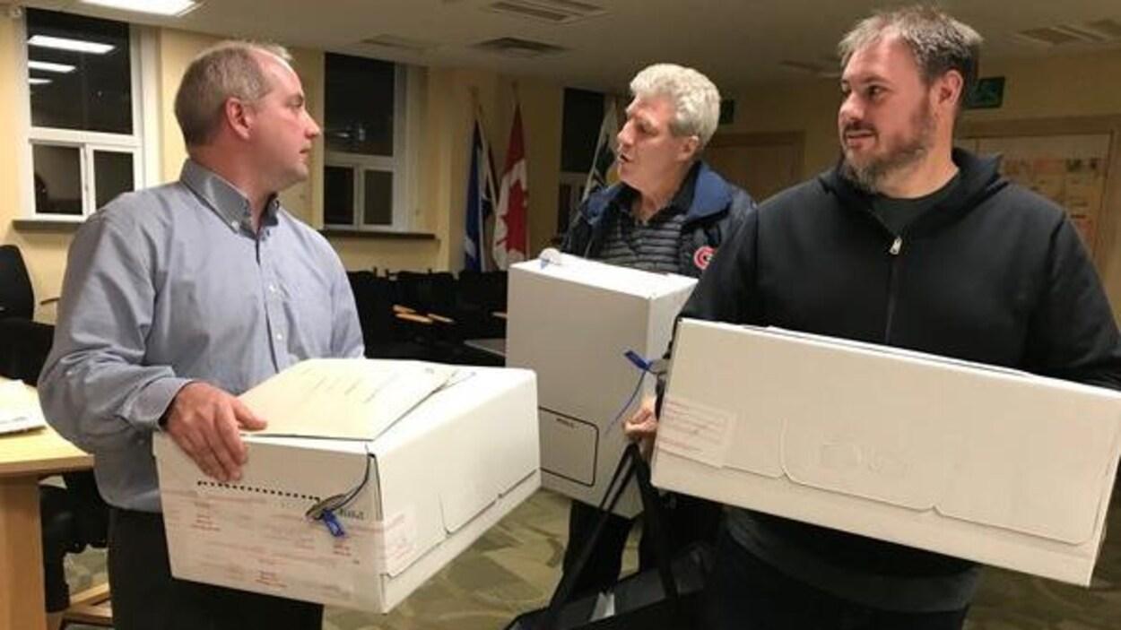 trois hommes avec des boites.