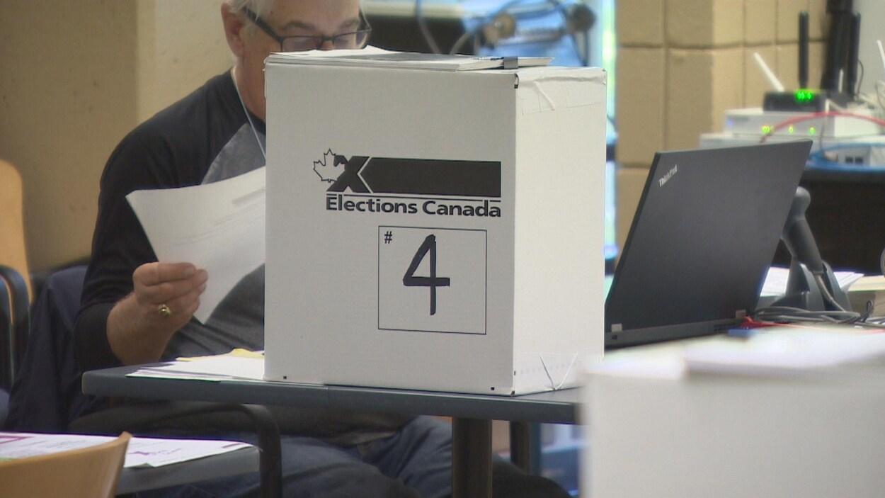 Sur un bout de table est posée une boîte en carton estampillée Élections Canada.