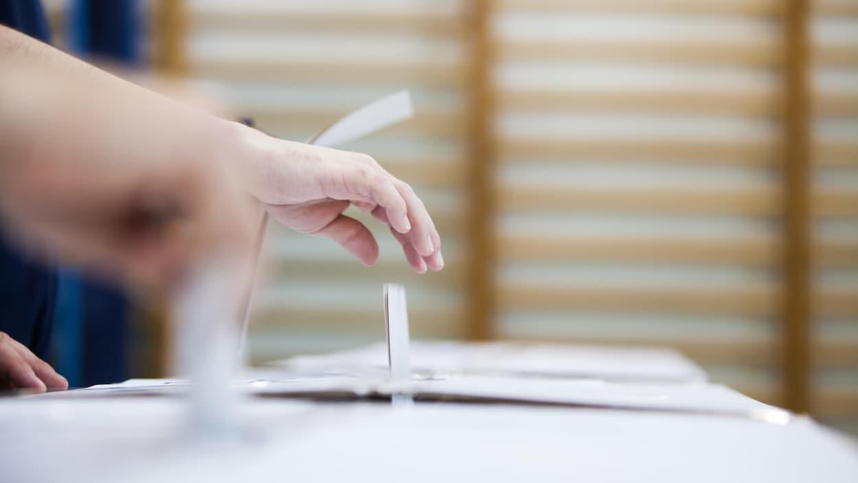 Un bulletin de vote est déposé dans une boîte de scrutin.