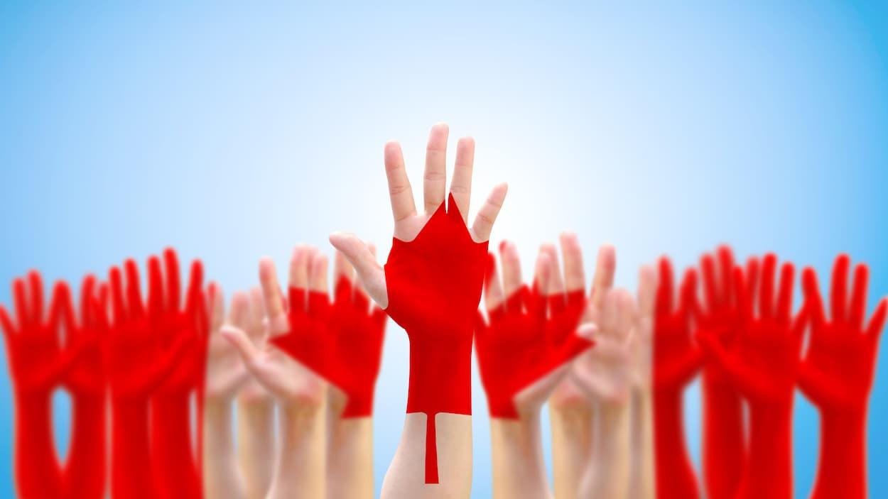 Des mains levées avec le motif d'un drapeau canadien en surimpression.