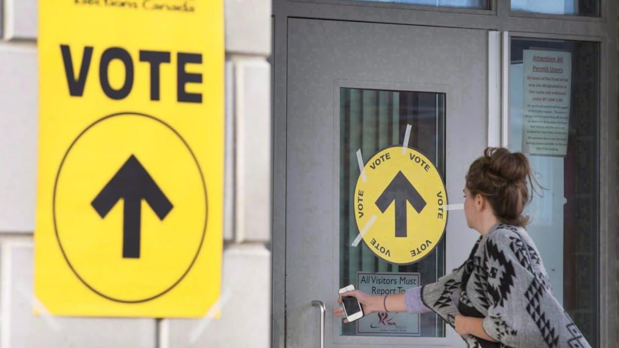 Une femme entre dans un bureau de vote.